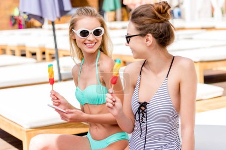 beautiful young women in swimsuit and bikini with popsicles sitting on sun lounger at poolside