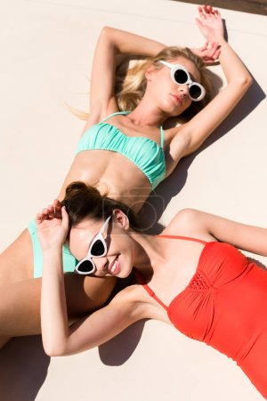 high angle view of beautiful young women tanning on light surface