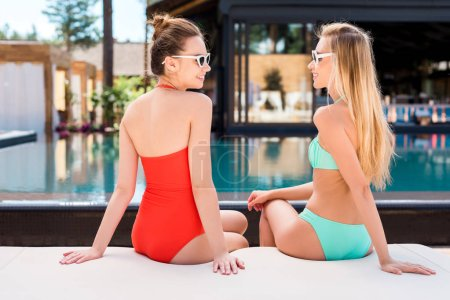 rear view of attractive young women relaxing on sun lounger at poolside and looking at each other