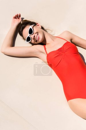 high angle view of happy young woman in red swimsuit lying on light surface