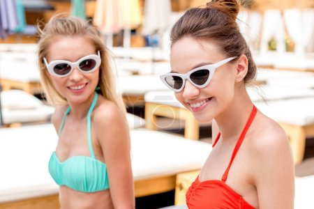 smiling young women in vintage glasses looking at camera at poolside