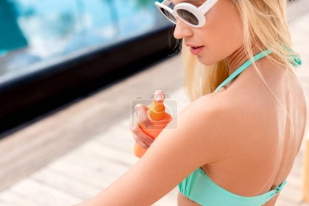 Photo for Close-up shot of beautiful young woman applying sunscreen onto skin from spray bottle - Royalty Free Image