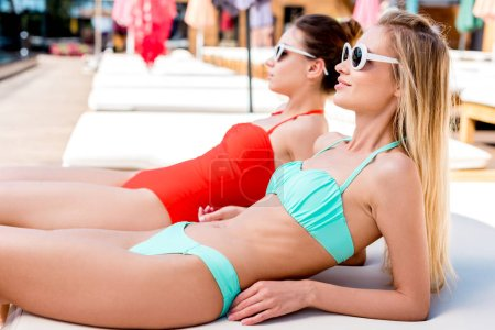 attractive young women lying on sun lounger at poolside