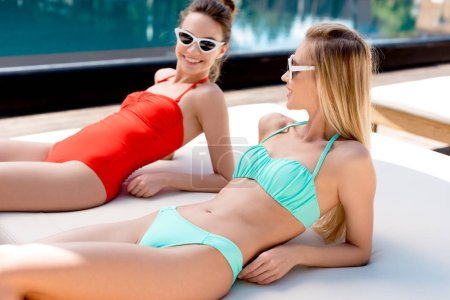 smiling young women relaxing on sun lounger at poolside and looking at each other