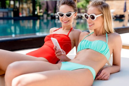 smiling young women using smartphone while relaxing on sun lounger at poolside