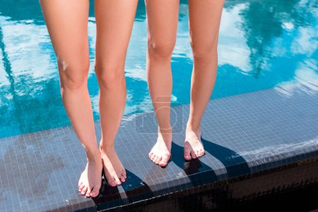 cropped shot of bare women standing on poolside