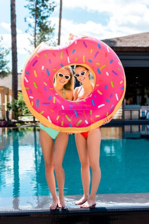 smiling young women looking at camera through inflatable ring in shape of bitten donut at poolside