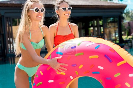happy young women with inflatable ring in shape of donut standing at poolside and looking away