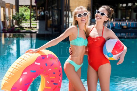 attractive young women with inflatable ring in shape of donut and beach ball standing at poolside