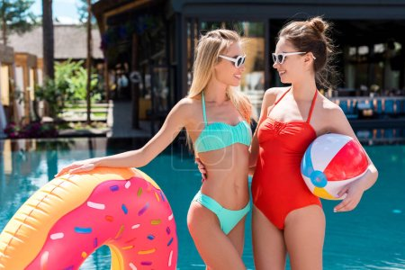 beautiful young women with inflatable ring in shape of donut and beach ball standing at poolside and looking at each other