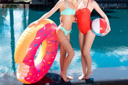 cropped shot of women with inflatable ring in shape of bitten donut and beach ball standing at poolside