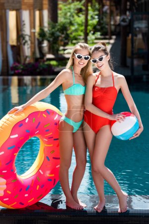 smiling young women with inflatable ring in shape of donut and beach ball standing at poolside