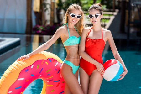 happy young women with inflatable ring in shape of donut and beach ball standing at poolside