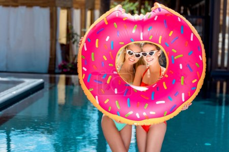 beautiful young women looking at camera through inflatable ring in shape of bitten donut at poolside