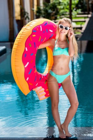 smiling young woman inflatable ring in shape of donut at poolside