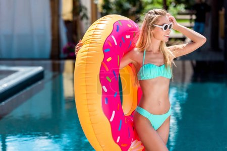 attractive young woman inflatable ring in shape of donut at poolside