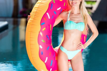 cropped shot of young woman inflatable ring in shape of donut at poolside