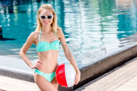 smiling young woman with beach ball at poolside looking at camera