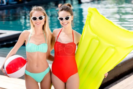 smiling young women with inflatable mattress and beach ball standing at poolside