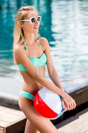 beautiful young woman with beach ball at poolside