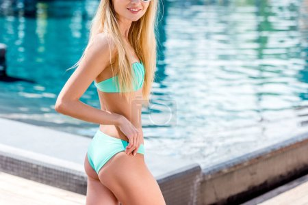 skinny young woman in bikini and vintage sunglasses at poolside