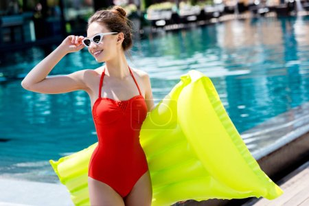 smiling young woman in red swimsuit with inflatable mattress standing at poolside and looking away