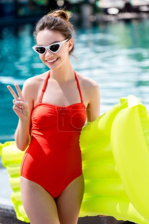 smiling young woman in red swimsuit with inflatable mattress standing at poolside and showing peace gesture