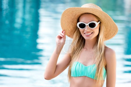 beautiful young woman in straw hat with vintage sunglasses and bikini at poolside
