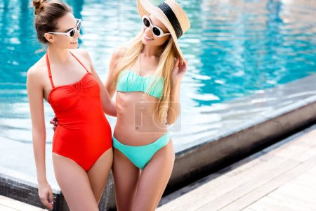 attractive young women in vintage sunglasses standing at poolside