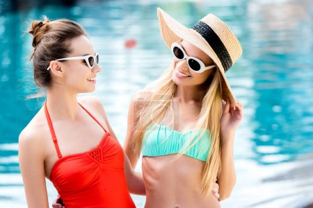 happy young women in vintage sunglasses standing at poolside