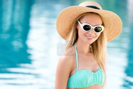 Photo for Smiling young woman in straw hat with vintage sunglasses and bikini at poolside - Royalty Free Image