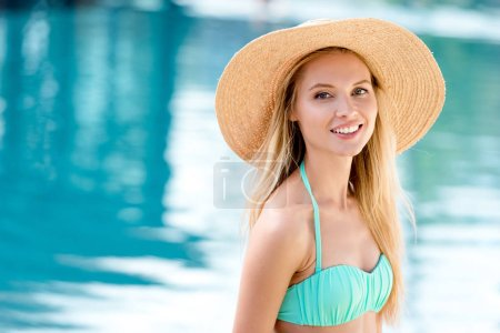 attractive young woman in straw hat and bikini looking at camera at poolside