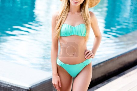 Photo for Cropped shot of young woman in straw hat and bikini at poolside - Royalty Free Image