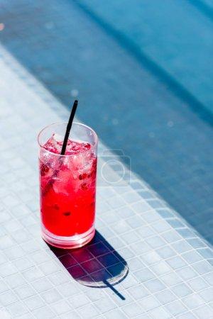 primer plano de vaso de cóctel de bayas en la piscina