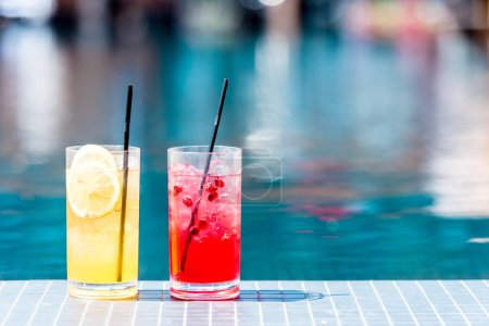 close-up shot of glasses of delicious red and orange cocktails on poolside