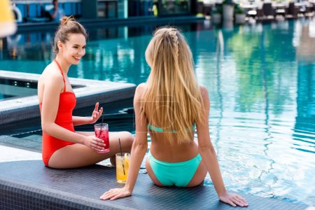 happy young women with delicious fruit beverages relaxing at poolside