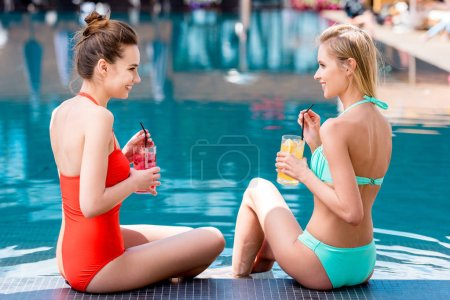 smiling young women with delicious fruit beverages relaxing at poolside