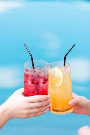 cropped shot of women clinking glasses of cocktails in front of swimming pool