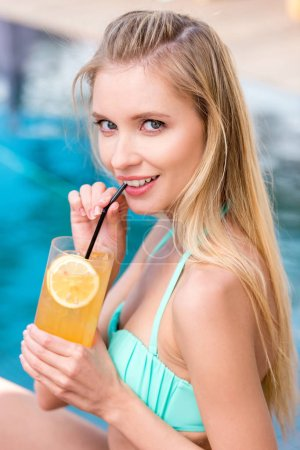 beautiful young woman with refreshing orange beverage looking at camera at poolside