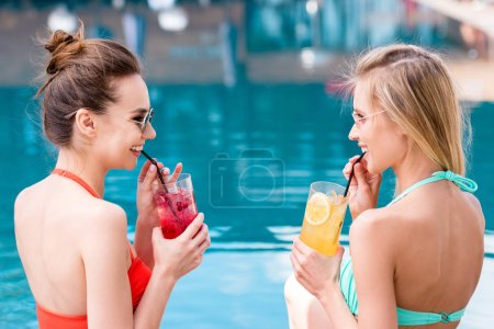 beautiful young women drinking delicious fruit beverages at poolside and laughing