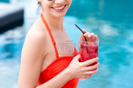 cropped shot of smiling young woman with berry cocktail at poolside