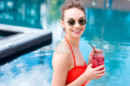 happy young woman in vintage sunglasses with berry cocktail at poolside