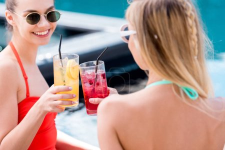 beautiful young women clinking glasses of cocktails at poolside