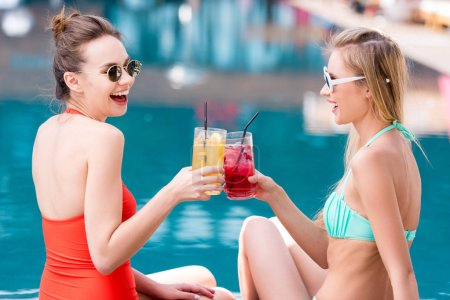 side view of attractive young women clinking glasses of cocktails at poolside