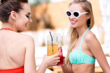 happy young women clinking glasses of cocktails at poolside