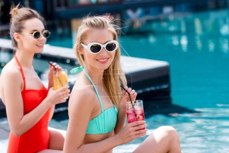 stylish young women with delicious fruit beverages sitting at poolside