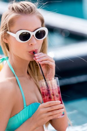 beautiful young woman in vintage sunglasses with berry cocktail at poolside