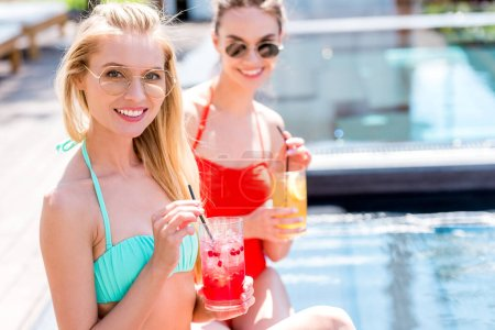 happy young women with delicious fruit beverages sitting at poolside and looking at camera