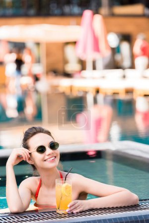 beautiful young woman with delicious orange cocktail relaxing at poolside