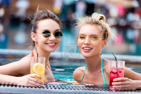 happy young women with delicious cocktails relaxing in swimming pool